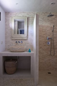 White cement walls, beige marble sink and wall tiles, pebble floor by True Ibiza
