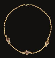 A GREEK GOLD AND GARNET NECKLACE   HELLENISTIC PERIOD, CIRCA 2ND CENTURY B.C.   Composed of biconical beads with a plain wire ring at each end, interspersed with three gold and garnet elements, each lozenge-shaped, formed of two stout wires voluted and beaded at their ends, embellished with filigree rosettes in each corner, an oval cabochon garnet in the center, the bezel encircled with beaded wire, a palmette of filigree beaded wire at each side; strung with a modern hook-and-loop closure
