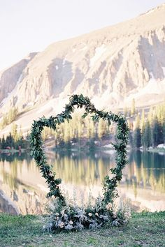 Organic Mountain Wedding Inspiration with a beautiful crest shaped ceremony background garland framing mountains and lake
