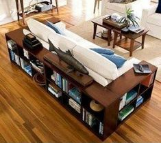 Bookshelves wrapped around couch    Forget end tables. These bookshelves fulfill