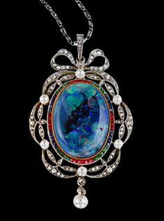 The platinum oval pendant encloses a black opal surrounded by a line of rubies, sapphires and emeralds within a diamond and pearl leaf and ribbon border tied with a bow knot to the top Circa 1910