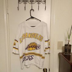 Vintage L.A. Lakers jersey-style shirt Awesome L.A. Lakers shirt. I love it to death, but we've moved into Spurs country and there's noooooo wearing a LAKERS shirt in Spurs country. :( The material has no tags, but I believe it's made of cotton. Definitely machine washable.  Sleeves stop just below the elbows. The front hem bottom rises just a little more than the back, giving it a cute and feminine look while still being sporty.  Excellent addition to the collection of any Lakers fan…