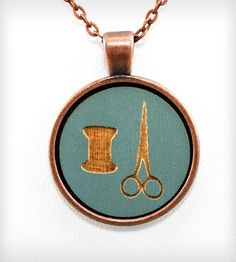 "Thread & Scissors Pendant Necklace by Once Again Sam on Scoutmob Shoppe ~ ""This cameo necklace features a hand-painted slate blue round wood pendant that is laser engraved with a spool of thread and a pair of scissors. The wood is set in copper and hangs from an aged copper chain with lobster clasp closure."""
