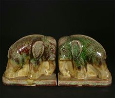 A pair of Denby Danesby Ware Moorland elephant book ends designed by Donald Gilbert, covered in a green and sang de boeuf crackled glaze printed marks 14.5cm. high