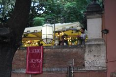 Restaurant owners of Trastevere's Risorante  Sottosopra smile as they wait for customers on a cool and partly cloudy October evening. The patio is lit up, welcoming their diners to enjoy eat and the autumn breeze with them.