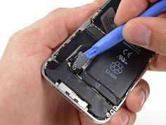 * Använd ett öppningsverktyg för iPod för att försiktigt bända upp batterikontaktens övre och nedre ändar.  * Var försiktig så att bara batterikontakten i silver lossas och inte den svarta kontakten på logikkortet. Om man försöker lossa kontakten på logikkortet kan man bryta sönder kontakten.  * Bänd inte mot kontaktclipsen  * Ta bort kontaktclipsen från iPhone.
