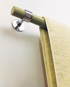Sleek towel bars are inexpensive wooden dowels painted in a yellow-green latex and mounted with chrome curtain hardware.