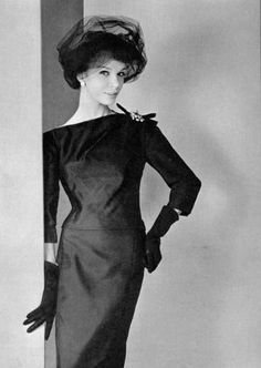 1958  Photo Philippe Pottier  Black satin dinner dress with an assymetrical neckline by Jean Patou.