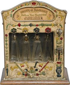 1 Cent Mills Novelty Whiffs Of Fragrance Perfume Spray Your Handkerchief Vending Machine c1916, fancy cast-iron front, oak case.  The vendor offered a choice of 4 fragrances, the customer would turn the indicator to the desired essence and pull the handle.  The perfume then sprayed out of a flower above the bottle holding the customers selection, in original condition, rare - 12w x 9d x 17h