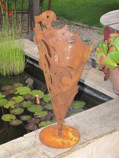 Metalltüte Barock aus Edelrost  Schöne, rustikale Metalltüte mit barockem Muster in Edelrost, die auf einer Platte befestigt ist. Die Tüte läßt sich schön bepflanzen oder kann auch mit einer Brenngeldose wunderbar beleuchtet werden.  Größe:  Höhe: 52 cm Durchmesser: 20 cm