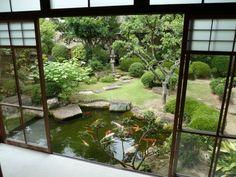 un jardin japonais avec un pavillon sur étang avec poissons rouges