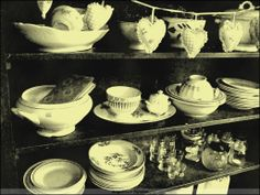 """Foto in ouderwets """"sepia"""" kleuren.  kast met ladeplanken vol met oud huishoudelijk aardewerk."""