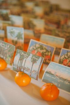 Love these escort cards - post cards in oranges. So fun! | Five ways to incorporate fruit wedding decor into your big day via @weddingpartyapp