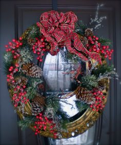 Old chippy oval picture frame turned into holiday wreath with some simple, store bought ribbon, greens and berries.