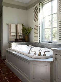 All the Extras The elegant surround with recessed panels is topped with elegant stone, a style repeated on the storage cabinets flanking the tub.