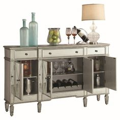 The Mirrored Wine Cabinet has a clean design with a shimmering platinum finish. Features 4 cabinet doors with silver pull knobs and mirrored fronts. Tapered legs with subtle details. The 3 shelves, 3 drawers, and inner bottle storage to keep all your wine essentials in one chic spot. Bailey Mirrored Wine Cabinet with Bottle and Glass Storage | Weekends Only Furniture and Mattress
