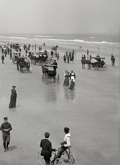 Daytona Beach remains famous for the ability of visitors to drive on the beach and get in a good dose of people-watching and flirting as they cruise.  This photo (circa 1904) shows that even then, bicycles and horses and buggies were allowed to cruise the beach!