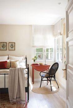 Dormitorio con mesilla de noche abatible antigua en rojo, silla negra Undredal de Ikea, alfombra natural y cama con estructura metálica en negro