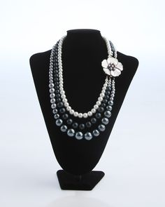 Vi Bella Jewelry - Rilyn Necklace - Embrace a fashion-forward sense of style! The Rilyn Necklace consists of three strands of pearls in various sizes and in hues of white, black, and grey. A large offset pearlescent flower clasp is an amazing focal point. Wear with Rilyn Earrings to make the most simple dress or outfit look simply stunning.     Length - 25 Inches     Handcrafted by Vi Bella Artists in Haiti.  $42.95