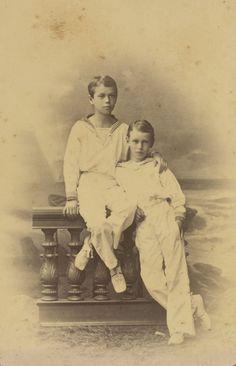 Czarevich Nicholas, depois, Nicolau II, e Grão-Duque George Alexandrovich. Czarevich Nicholas está sentado em uma balaustrada com o braço esquerdo em torno de Grão-Duque George que está em pé ao lado dele para a direita. Ambos os meninos estão vestindo ternos de marinheiro. Há um cenário pintado do mar atrás. Em 1883.