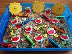 Back to School Sensory Bin - It contains rainbow dyed rice (dyed with kool aid for additional sense of smell), various erasers (suns, apples, A+, smiley face, stars, and crayons) and apple gems - Back to School Sensory Activity