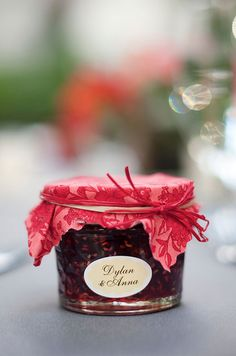 Guests are sent home with amazing handmade jam topped with floral fabric and raffia.