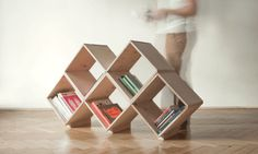 """A well thought out shelving construction, comprised of several sets of L-shaped wooden components, is being secured in place by screws and rested upon wooden stands. So, in spite of its weightless looks, the unit can withstand a good load of books, DVDs, CDs, periodic marials and small items."""