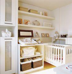 00144624. Dormitorio infantil en tonos beige y blanco con una cuna y varios cuadros pequeños sobre una estantería_00144624