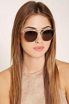 A pair of aviator sunglasses with matte metal accents at the top of each lens…