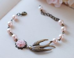 This is a vintage and nature inspired, romantic bracelet. It is made from Swarovski ivory pearls and a antiqued brass leaf. A peach pink resin flower is securely set on the leaf. Beautifully hammered brass link chain with a small pearl is added to one side of the bracelet so that you can easily adjust the length to best fit your wrist. Length: adjustable between 6 inches and 9 inches (15cm -23cm) Pearls: 6mm Resin flower: 13mm Brass leaf: 38mm long, 20mm wide  The last picture shows a large…