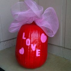 """Repurposed Halloween pumpkin. My daughter decorated this pumpkin before halloween with markers and stickers. We painted it a bright red for Christmas and placed a christmas bow on top (like a present). Now that Christmas is over and valentines day is next we added pink hearts and """"love"""" to transform the pumpkin once again. A great way to reduce and reuse:)"""