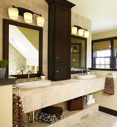Sticking to the same materials—wood in the vanity and medicine cabinet, glass on the counter and shelves—keeps the tone consistent. Using shades of the same color (in this case, gray) throughout the surfaces keeps the space coordinated.