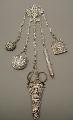 A Victorian chatelaine by Charles Miller, London 1890. The cast and chased belt attachment depicting two winged cherubs, with five original attachments; a notebook, a propelling pencil, a scissors holder (steel scissors), a circular pin cushion and a pill box, by another, Birmingham 1901.
