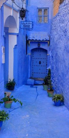 Blue side alley with hotel entry door - Chefchaouen, Morocco by Raph Ledergerber