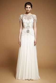 "Brides.com: . ""Damask"" chiffon A-line wedding dress with a beaded bodice, high neckline, and short sleeves, Jenny Packham"