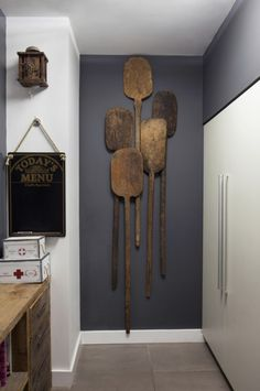 Antique wooden paddles hang from a gray wall, along with several other accent pieces