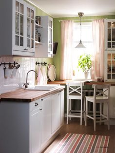IKEA kitchen that fits most of what I want in our kitchen- paint the beadboad green, butcher block countertops, white cabinets and appliances and a farmhouse sink. With the Aga stove... When I win the lottery, or a fix my ugly kitchen contest.