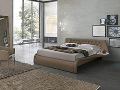 El dormitorio es una habitación moderna y cómoda con una cama matrimonial en el centro, dos alfombras, un espejo y unas sillones. Además, hay unos cuadros colgados en la pared y la habitación comunica también con una veranda.