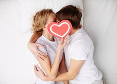 couple laying in bed on valentine's day holding a paper heart