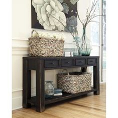 Ashley Furniture Gavelston Sofa Table Tables are made with select veneer and solids in a dry vintage weathered black finish. Framed drawers and aprons. Small wrought looking dark bronze color accent…