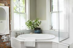 This bathroom in a romantic Victorian home has a corner bathtub, potted plant, glass partition, oval mirror, exposed brick, gray walls, and lots of natural light.