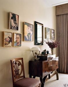 A collection of Elizabeth Peyton portraits—including one of Jacobs—is clustered on a hallway wall. The cabinet and mirror are by Eugène Printz. The André Groult chair is from Maison Gerard.