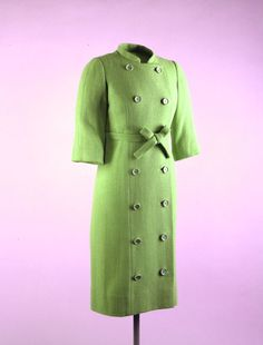 """Pistachio Green Coat Maker: Gustave Tassell (American, 1926 - ) Date(s) of Materials: 1961 Place Made: United States Medium: Wool boucle Dimensions: 42"""" center back Description: A double breasted coat of pistachio green wool boucle with a mock collar, three-quarter length sleeves, and a belted waist. Twelve buttons on front lapel accent the line of the coat from collar to hem. Historical Note: This coat was worn by First Lady Jacqueline Kennedy on her arrival at the Bogota airport."""