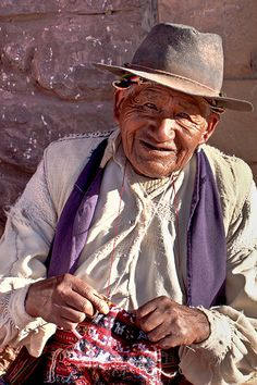 Old man knitting, Tacile island, lake Titicaca , Peru.