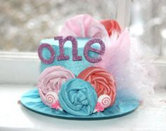 Adorable Alice in Wonderland inspired Mini Top hat - shades of pink. Bits of tulle, fabulous feathers, and sparkly rosettes. Perfect for that little ladys photo shoot, a birthday party, or as an accent to a cute costume. Top hat measures 2 inches tall, with a base diameter of 5 inches. Comes attached to a soft elastic headband. Just what every little lady (or photographer) needs!    **SIZE:    Newborn - 13  3-6 months - 15  6 months - 12 months - 16  12 months - Teen - 17    Please indicate…