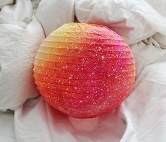 """This galaxy paper lantern was hand-painted to resemble space-like nebula patterns. This lantern measures 8"""" in diameter and is a combination of pink, yellow and orange with white."""