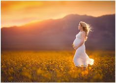 Beautiful pregnant woman in a white dress poses in a field of yellow wildflowers at sunset for her maternity portraits near Las Vegas. LJHolloway Photography is a Las Vegas Maternity Photographer.