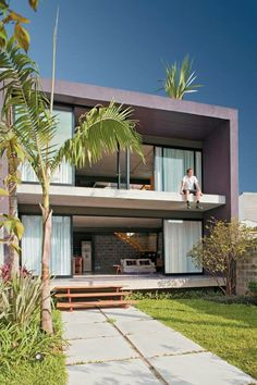 Sacada aberta de casa quadrada, com portas amplas e voltadas para o sol em ambos os andares.