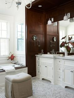 The inspiration for this posh paneled bath seems to be a dignified library or dining room. Dark mahogany walls and cool white tile, wainscoting, and cabinetry recall a dining room or traditional library. The cabinetry and tub surround are custom, creating a unified look for the room. Marble counters complete the luxurious look.