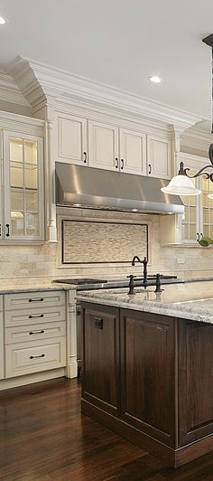 Off white kitchen with large stained wood island.
